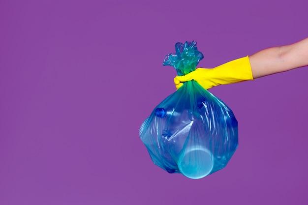 Una mano que lleva un guante de goma sostiene una bolsa de basura transparente Foto Premium