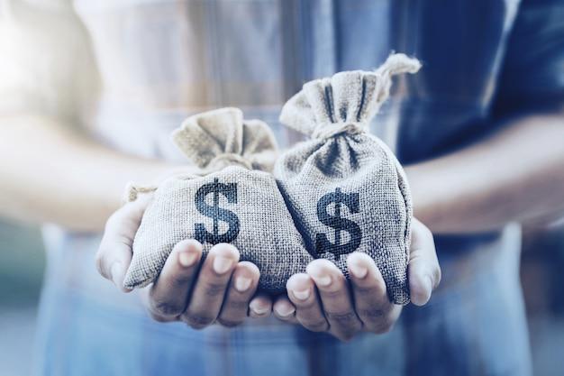 Mano que sostiene la bolsa de dinero. concepto de ahorro financiero y contable. Foto Premium