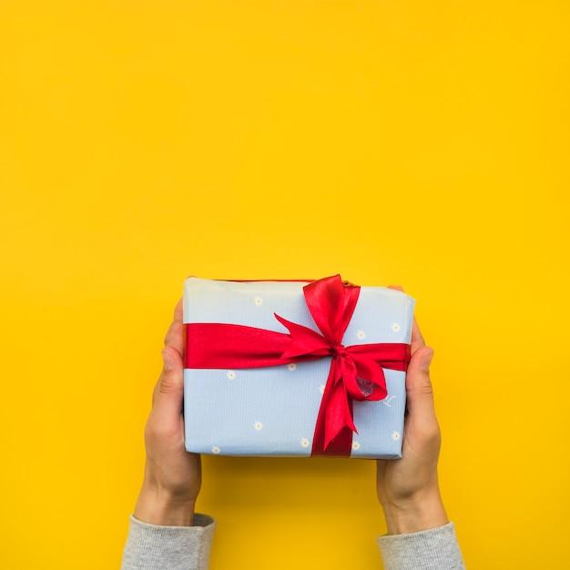 Mano que sostiene la caja de regalo envuelta con lazo de cinta roja sobre fondo amarillo Foto gratis