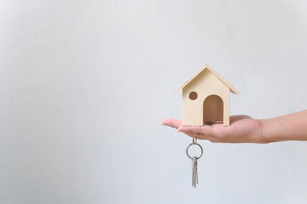 Mano que sostiene la casa de madera y el llavero de la casa. inversión inmobiliaria e hipoteca inmobiliaria inmobiliaria Foto Premium