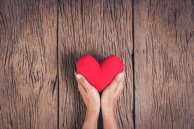 Mano que sostiene el corazón rojo sobre fondo de madera Foto gratis