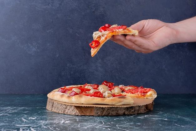 Mano que sostiene la deliciosa pizza de pollo con tomates en mármol. Foto gratis