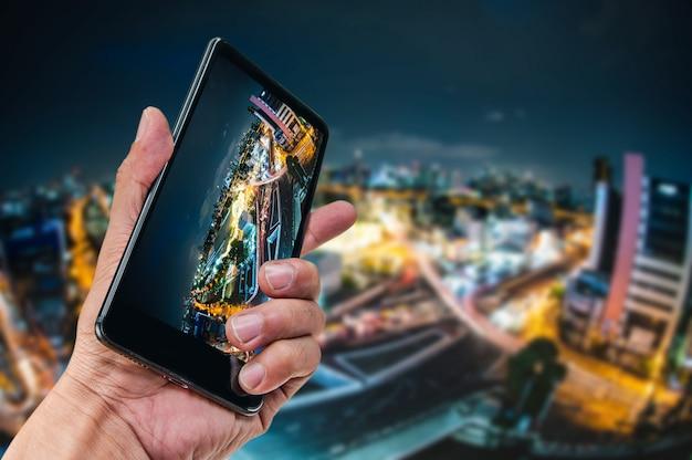 Mano que sostiene el fondo de la naturaleza del paisaje del smartphone Foto Premium