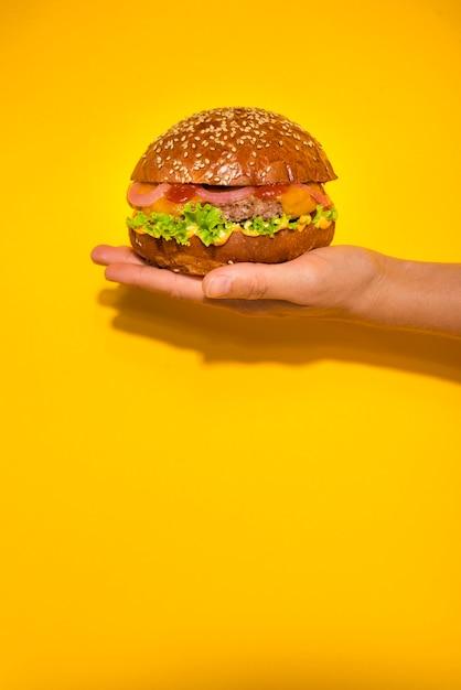 Mano que sostiene la hamburguesa de carne clásica con lechuga Foto gratis