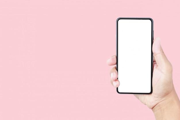 Mano que sostiene la maqueta del smartphone en fondo en colores pastel rosado con el espacio de la copia Foto Premium
