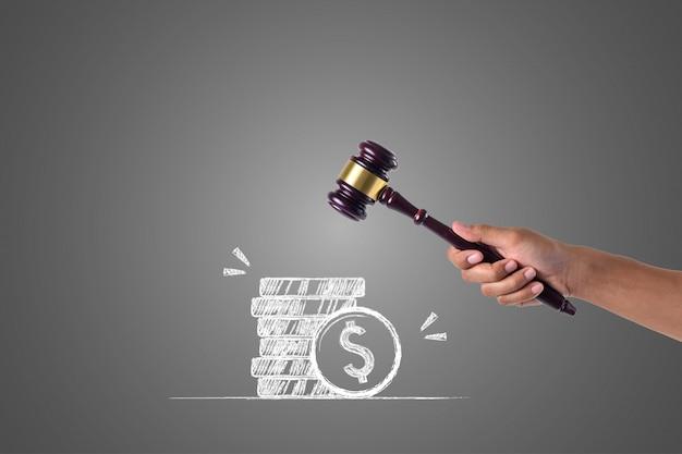 La mano que sostiene el martillo y las pilas de dinero escritas con tiza blanca, dibujan el concepto. Foto gratis