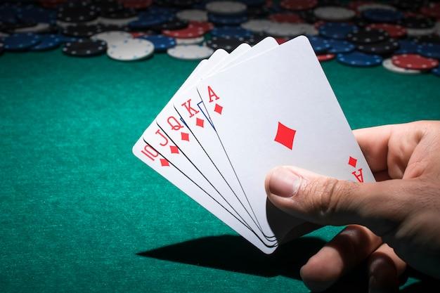 Mano que sostiene el naipe en la mesa de póquer Foto Premium