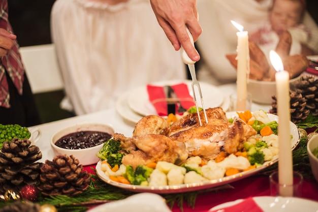 Mano que sostiene el pavo con un tenedor en la mesa de navidad Foto gratis