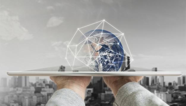 Mano que sostiene la tableta digital con tecnología de conexión de red global y edificios modernos Foto Premium