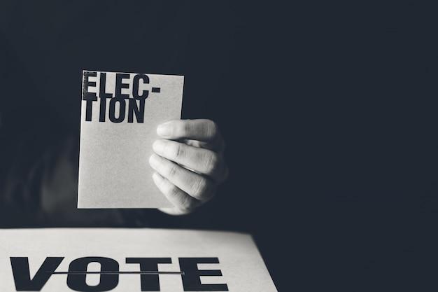 Mano que sostiene la tarjeta de la elección y el cuadro de votos, concepto de democracia, tono blanco y negro Foto Premium