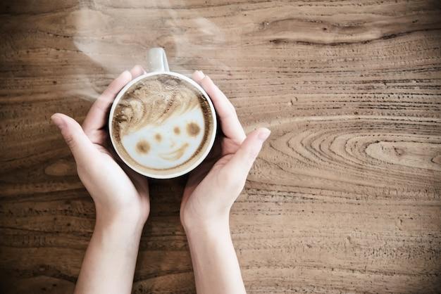 Mano que sostiene la taza de café caliente - personas con concepto de café Foto gratis