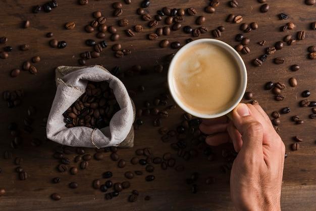 Mano que sostiene la taza con café cerca de saco con frijoles Foto gratis