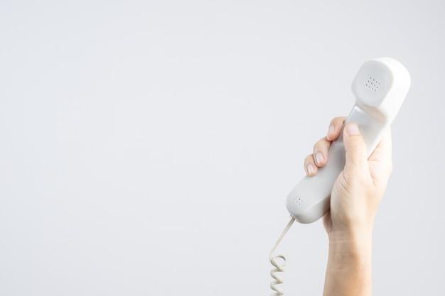 Mano que sostiene el teléfono de casa u oficina con línea Foto Premium