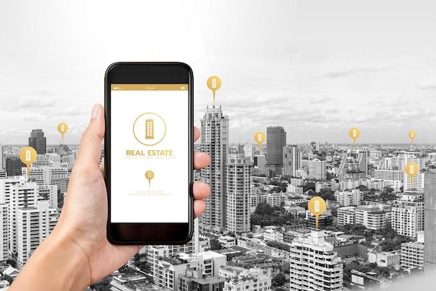 Mano que sostiene el teléfono inteligente con la aplicación para encontrar bienes raíces en la pantalla Foto Premium
