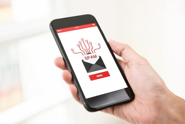 Mano que sostiene el teléfono inteligente que controla el correo electrónico no deseado en la pantalla Foto Premium