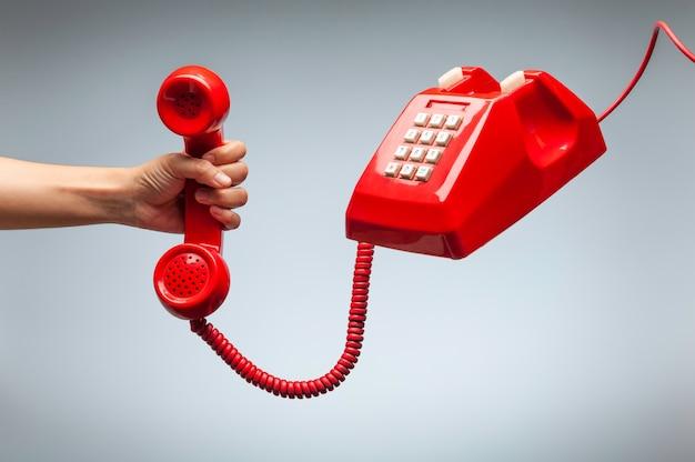 Mano que sostiene el teléfono, receptor de teléfono rojo clásico | Foto Premium