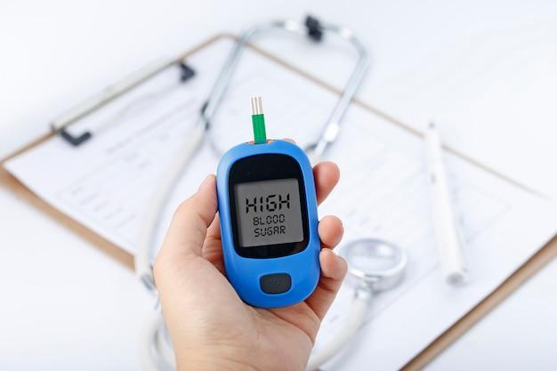 Mano que sostiene un medidor de glucosa de sangre que mide el azúcar de sangre, el fondo es un estetoscopio y un archivo de carta Foto Gratis