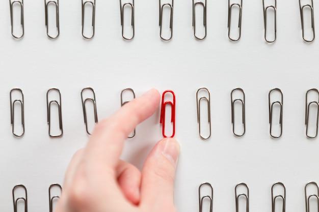 Mano recogiendo entre los clips de papel de metal uno rojo, diferente de otros Foto gratis