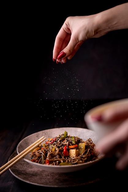 Mano rociando sal en un tazón de fideos con verduras Foto gratis
