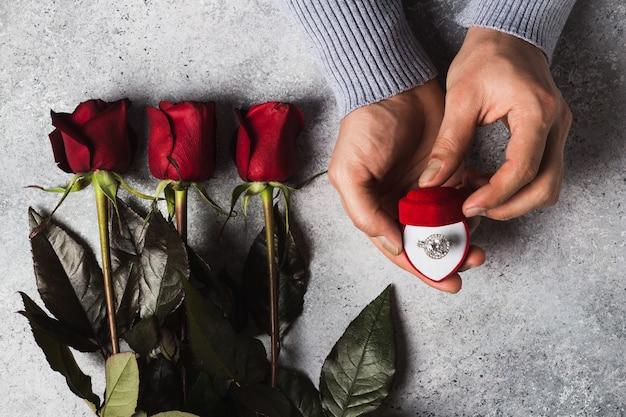 Mano romántica del día de san valentín que sostiene el anillo de compromiso en caja Foto gratis