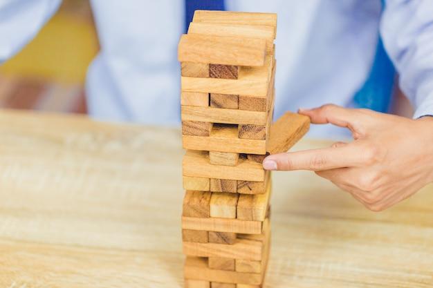 Mano sacando o colocando un bloque de madera en la torre, el plan y la estrategia en los negocios Foto Premium