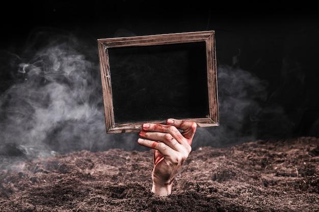 Mano en sangre saliendo de la tierra y con cartel negro Foto gratis