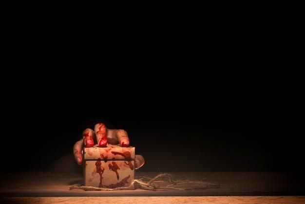 Mano sangrienta asustadiza sosteniendo una caja en la mesa de madera Foto Premium