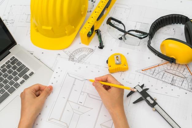 Mano sobre planes de construcción con casco amarillo y una herramienta de dibujo Foto gratis