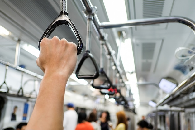 Mano sosteniendo un asa de tren de metro Foto Premium