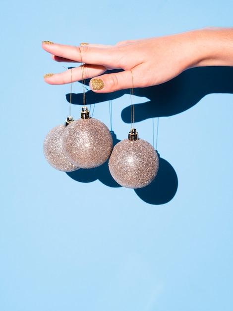Mano sosteniendo bolas de decoración Foto gratis