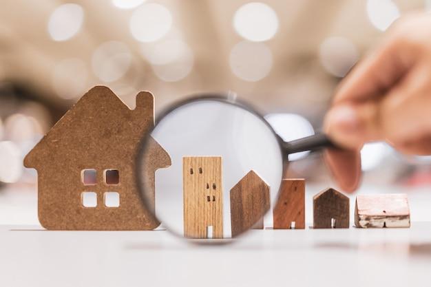Mano sosteniendo la lupa y mirando el modelo de la casa Foto Premium