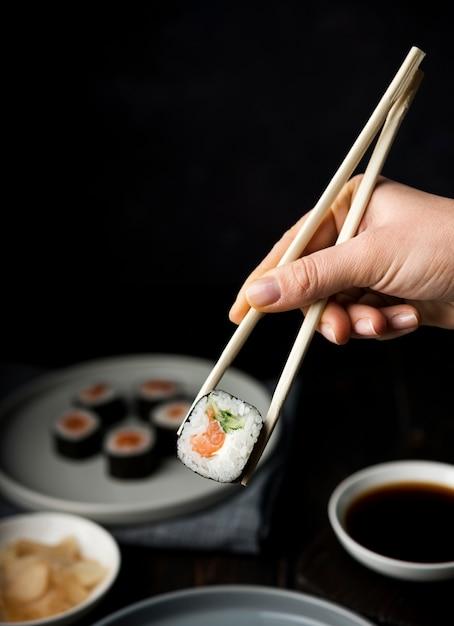 Mano sosteniendo palillos para rollos de sushi Foto gratis