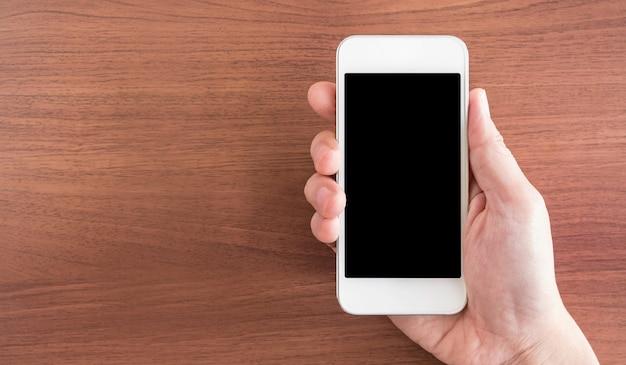 Mano sosteniendo la pantalla vacía del teléfono móvil sobre la mesa Foto Premium