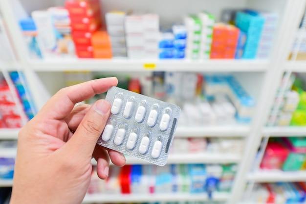 Mano sosteniendo el paquete de medicamentos en la farmacia farmacia Foto Premium