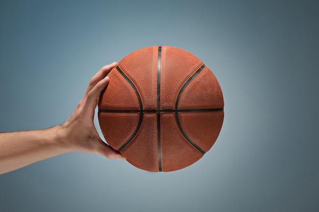 Mano sosteniendo una pelota de baloncesto Foto gratis
