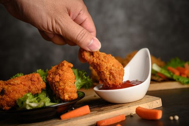 Mano sosteniendo pollo frito crujiente bañado en salsa de tomate Foto gratis
