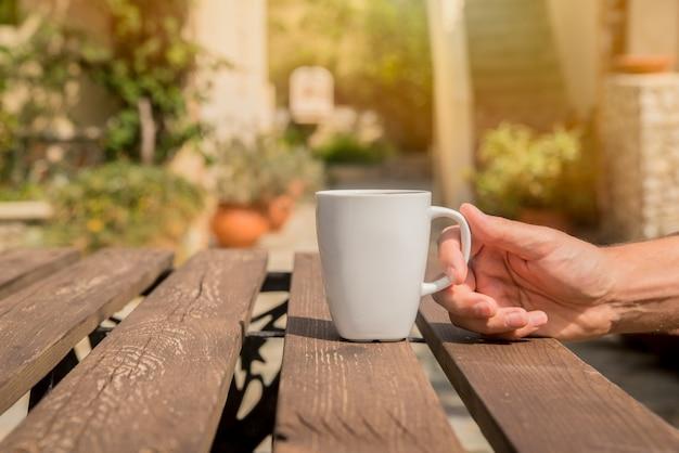 La mano está sosteniendo una taza de café. los hombres están bebiendo el café de la mañana con un fondo verde afuera. man manos sosteniendo taza de café en el verano al aire libre de café Foto gratis