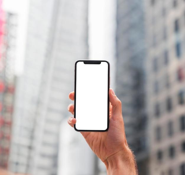 Una mano sosteniendo un teléfono inteligente en una calle de la ciudad Foto gratis