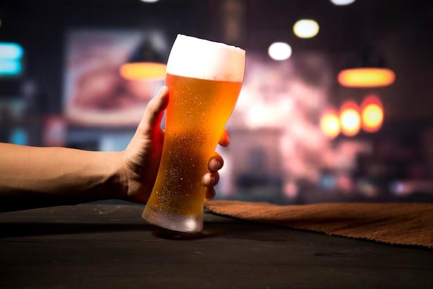 Mano sosteniendo vaso de cerveza Foto gratis