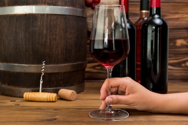 Mano sosteniendo vaso de vino con botellas y barril Foto gratis