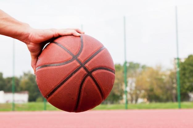 Mano sujetando pelota de baloncesto Foto gratis