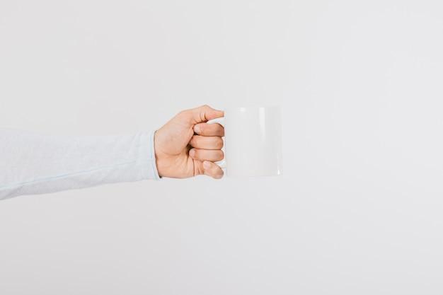 Mano sujetando una taza de café de perfil Foto gratis