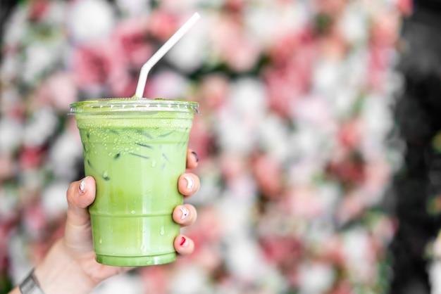 Mano sujetando la taza de té verde matcha latte helado Foto Premium