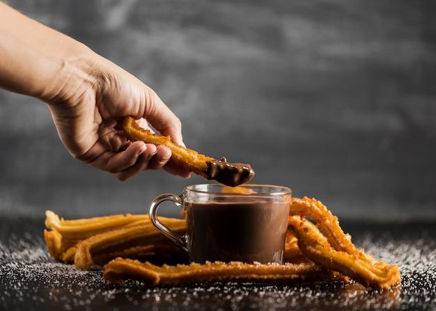 Mano sumergiendo un churros fritos en vista frontal de chocolate Foto gratis