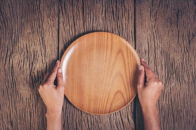 Mano superior de la visión que sostiene la placa en el fondo de madera Foto gratis