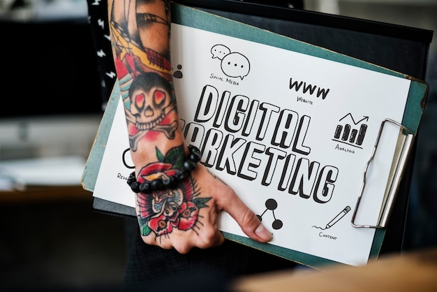 Mano tatuada sosteniendo un portapapeles de marketing digital. Foto Premium