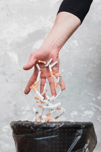 Mano tirando cigarrillos en la basura contra la pared vieja Foto gratis
