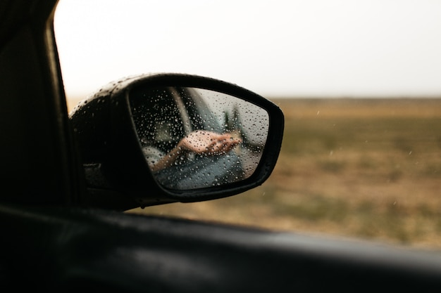 Mano tocando gotas de lluvia. espejo visto a través del cristal. ventana de coche mojada. ciérrese encima de la gota de lluvia. vista del coche ver el espejo. día lluvioso. Foto Premium