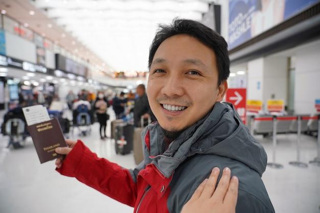 Mano tocando el hombro asiático para saludar a un amigo en el aeropuerto cuando espera el vuelo a bordo, pasaporte con equipaje grande, viajero y amigable Foto Premium