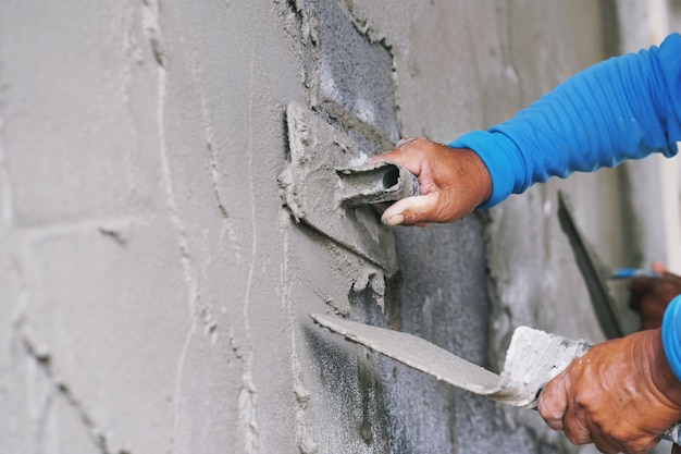 Mano del trabajador de enlucido de cemento en la pared Foto Premium